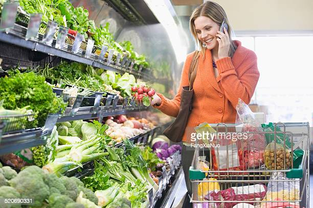 Woman talking on cell phone by vegetables in supermarket
