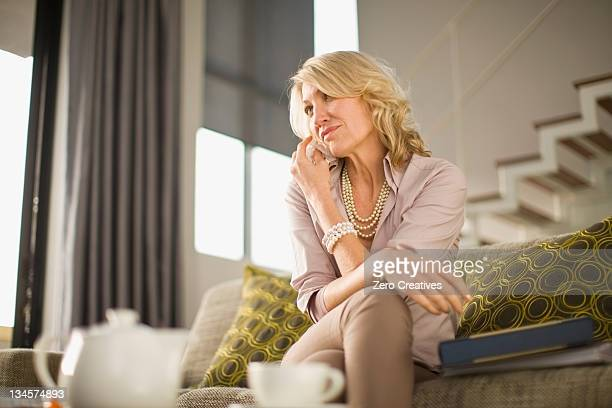 Woman talking on cell phone on couch