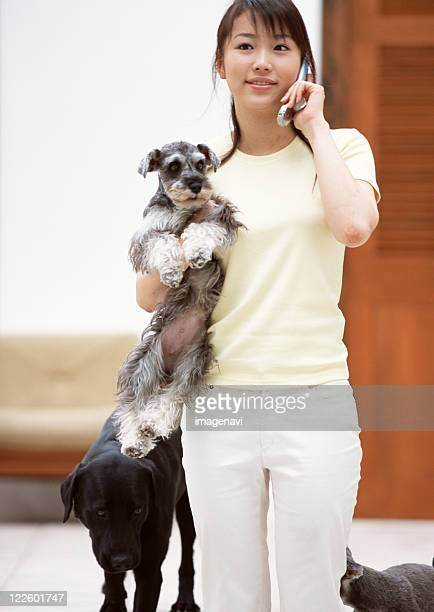 Woman talking on cell-phone with dogs