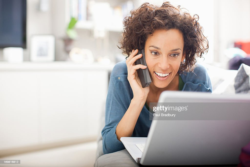 Woman talking on cellphone with laptop : Stock Photo