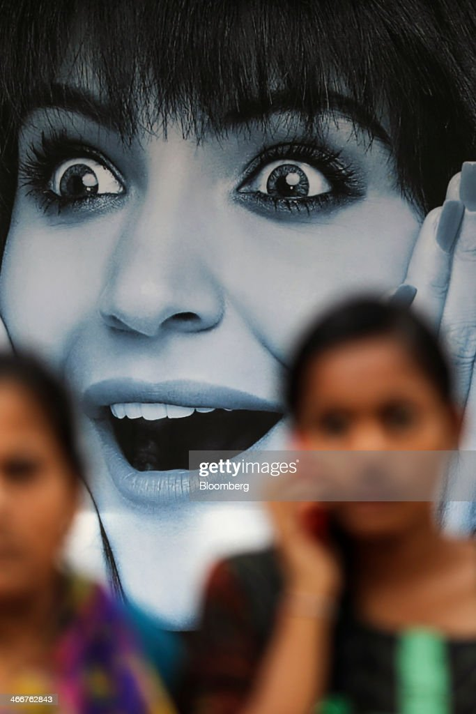 A woman talking on her mobile phone passes an advertisement in the window of a Reliance Communications Ltd. retail store in Mumbai, India, on Wednesday, Jan. 29, 2014. India got bids totaling 446.1 billion rupees ($7.12 billion) on the first day of a wireless spectrum auction on Feb. 3, the third effort by the government to raise revenue from the sale of airwaves in the last 15 months. Photographer: Dhiraj Singh/Bloomberg via Getty Images