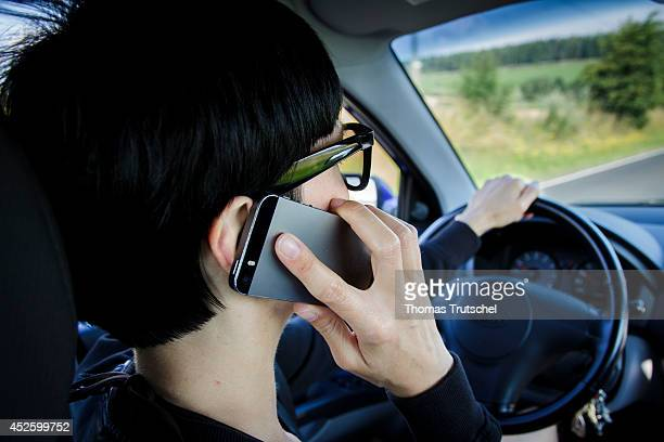 Woman talking on her mobile phone while driving a car on July 17 in Buecheloh Germany