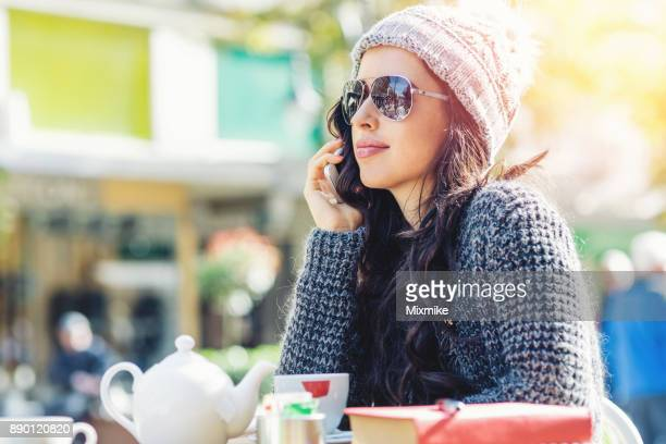 Woman talking on her mobile phone while having cup of tea
