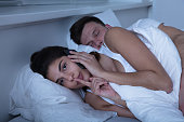 Young Woman Talking On Mobile Phone While Her Husband Sleeps On Bed