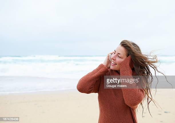 Woman talking on phone at beach.