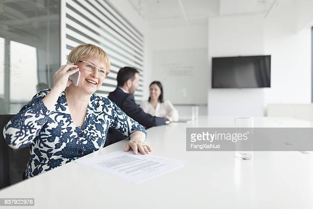 Woman talking on phone during business meeting