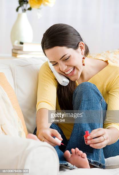 Woman talking on phone while painting toenails