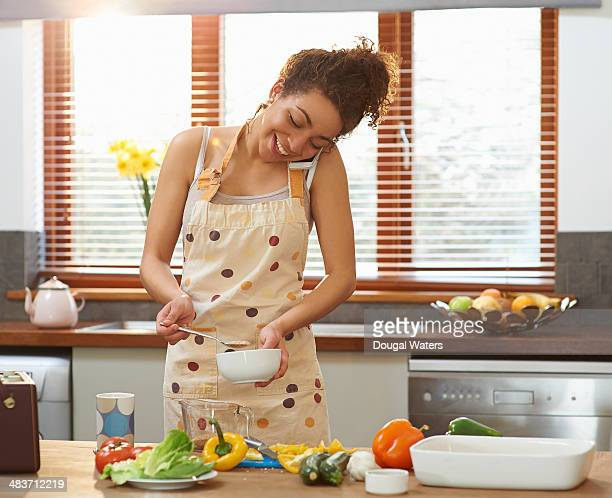 Woman talking on phone whilst cooking.