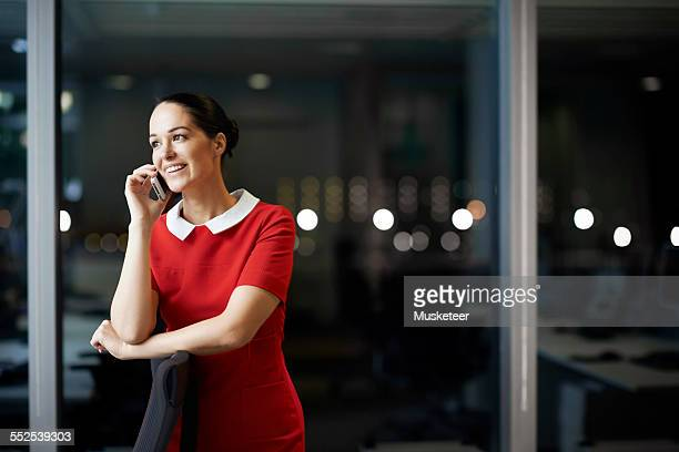 Woman talking on the phone in office at night