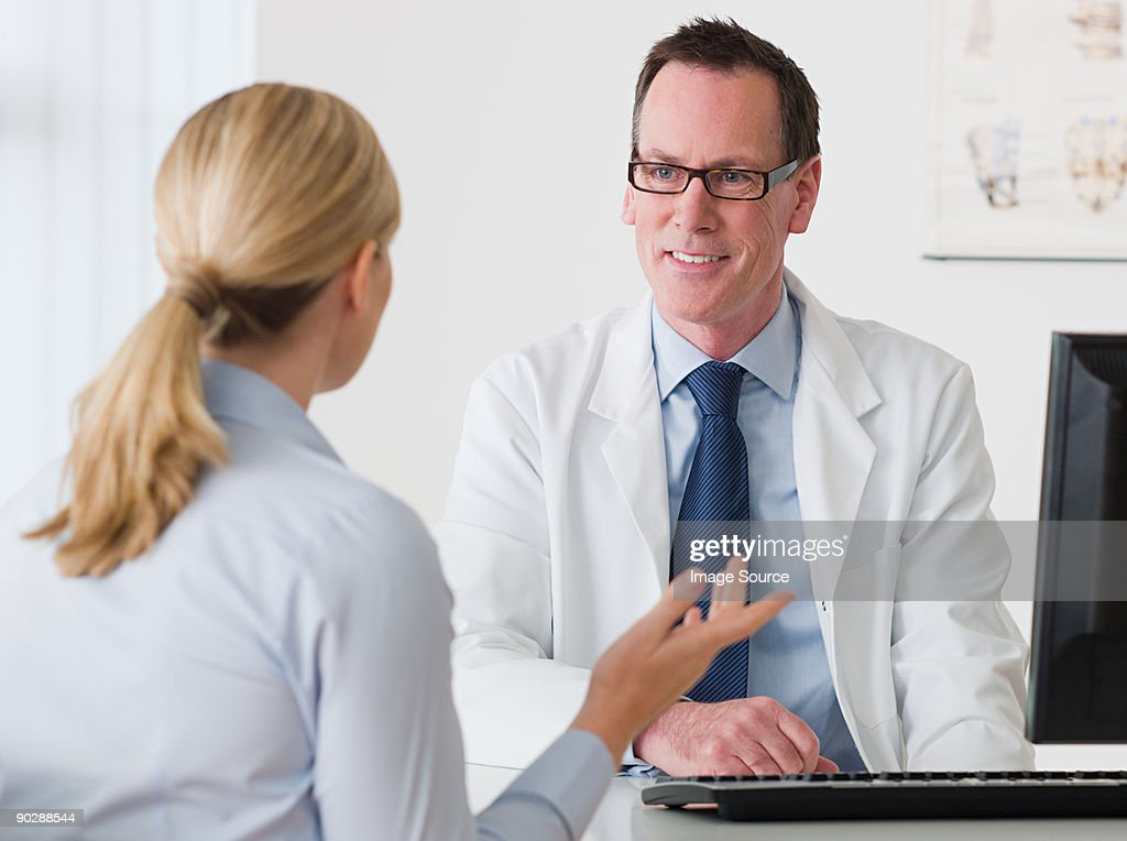 Woman talking to a doctor : Stock Photo
