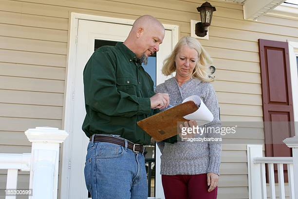 A woman talking to a home inspector on her front porch