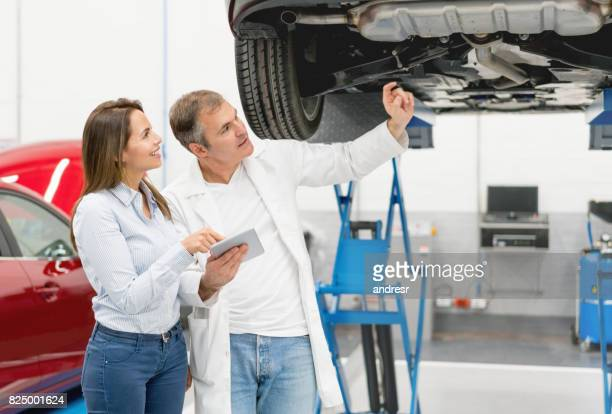Woman talking to a mechanic about her car at a garage