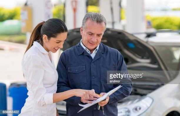 Frau, die ihr Auto zu einem Mechaniker reden