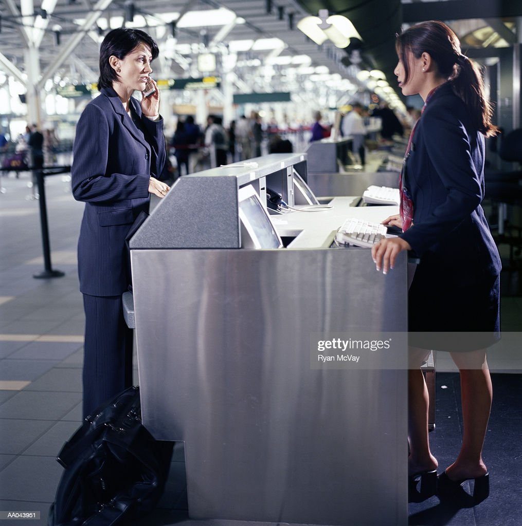 Woman talking to attendant at airport check-in counter, side view