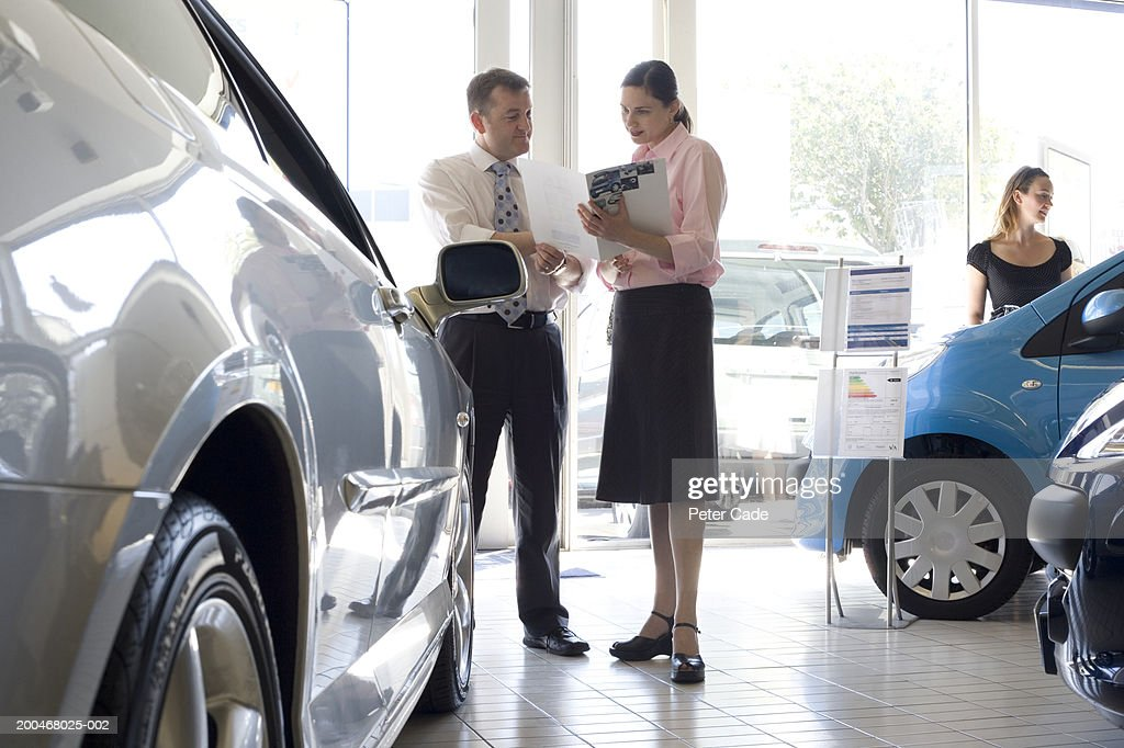 Woman talking to auto salesman in showroom : Stock Photo