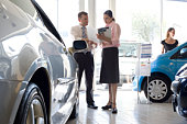 Woman talking to auto salesman in showroom