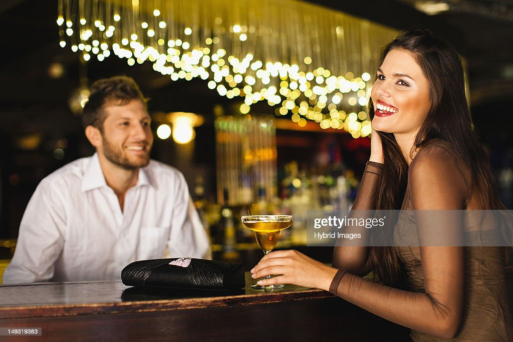 Woman talking to bartender at bar : Stock Photo