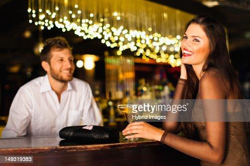 Woman talking to bartender at bar : Stock Photo