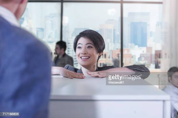 Woman talking to colleague in city office