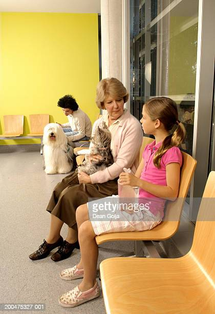 Woman talking to girl (9-11) holding goldfish in vets waiting room