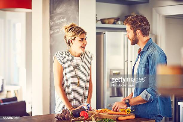 Woman talking to man cutting carrot at kitchen island