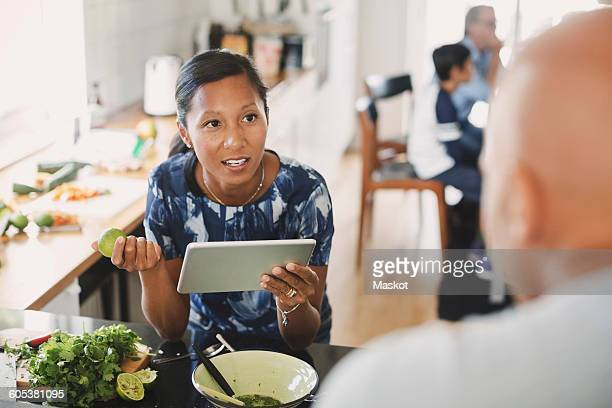 Woman talking to man while holding digital tablet in kitchen