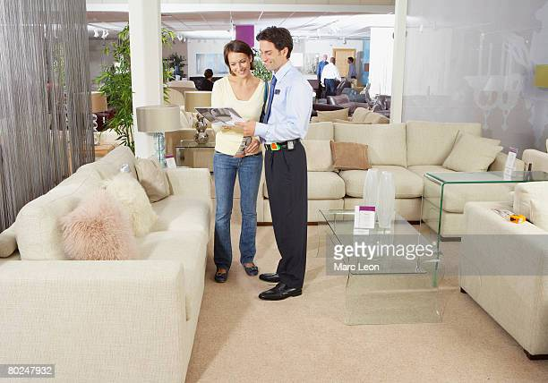 Woman talking to salesman in sofa shop.