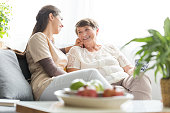 Woman talking with happy elderly mother while sitting on sofa at home during meeting