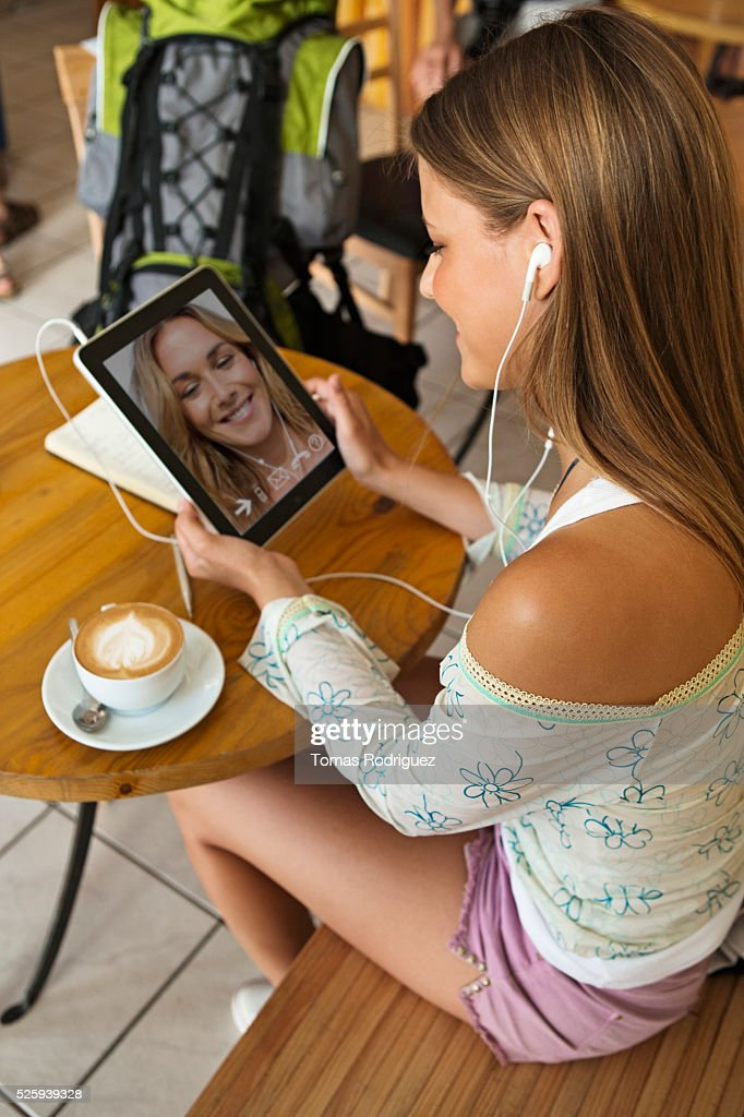 Woman talking with friend via digital tablet in cafe : Stock-Foto