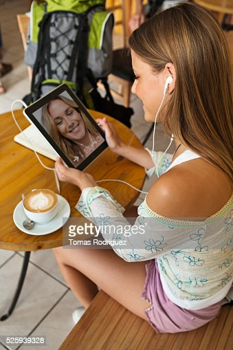 Woman talking with friend via digital tablet in cafe : Stockfoto