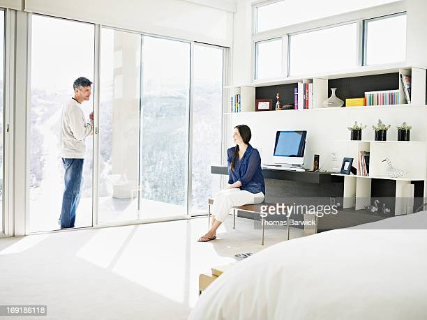 Woman talking with husband in modern bedroom