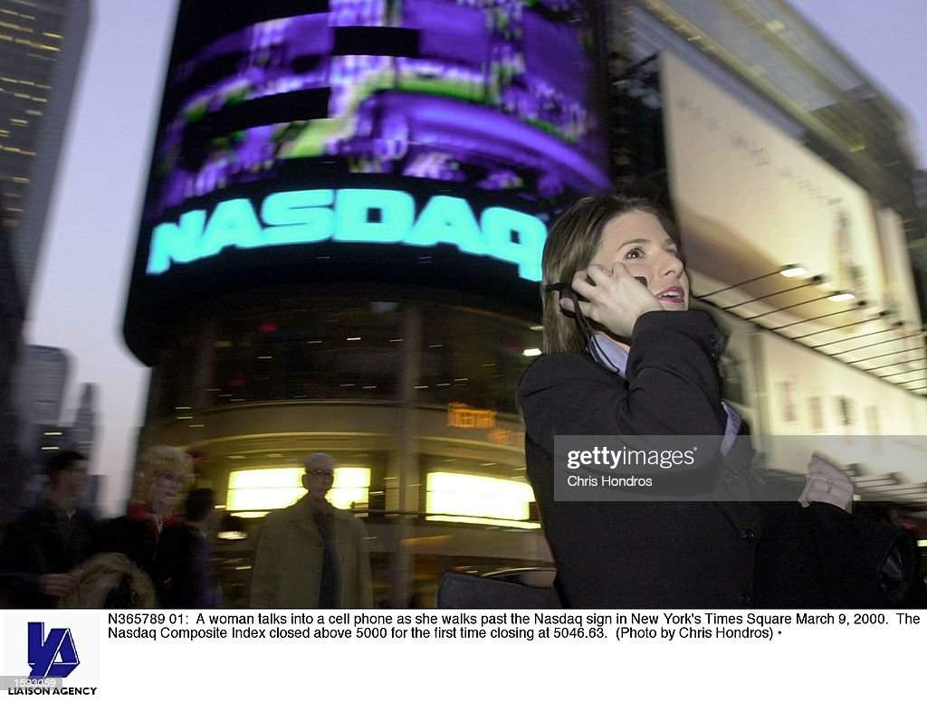 A woman talks into a cell phone as she walks past the Nasdaq sign in New York's Times Square March 9 2000 The Nasdaq Composite Index closed above...
