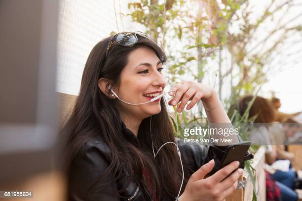 Woman talks into microphone of phone headphones, sitting in urban market.
