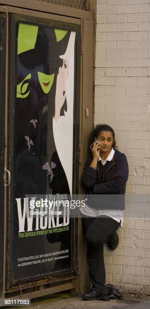 A woman talks on a cell phone next to a promotional billboard for the Broadway musical 'Wicked' as seen in this 2009 New York NY early afternoon...