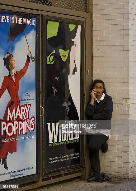 A woman talks on a cell phone next to a promotional billboard for the Broadway musicals 'Wicked' and 'Mary Poppins' as seen in this 2009 New York NY...