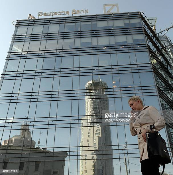 A woman talks on a mobile phone as she walks past a building that houses Deutsche Bank's Russian headquarters in Moscow on September 18 2015...