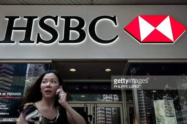 A woman talks on a mobile phone as she walks past a logo of HSBC outside a branch of the bank in Hong Kong on July 8 2014 Activists questioned an...