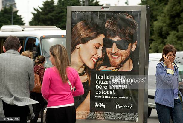 A woman talks on a mobile phone while passing by an advertisement for Telecom Personal SA a subsidiary of Telecom Italia SpA in Buenos Aires...