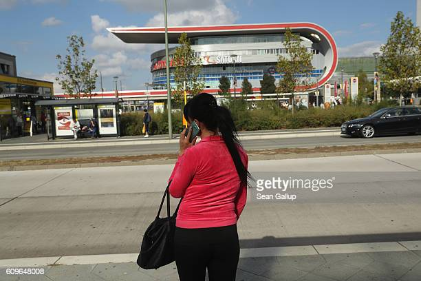 A woman talks on a mobile phone while waiting at a public bus station near the Eastgate shopping mall in Marzahn district on September 21 2016 in...