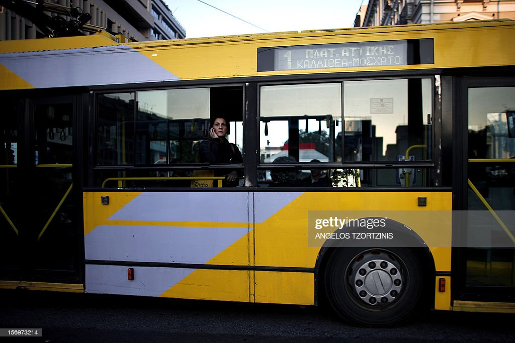 A woman talks on her cell phone as she stands in a bus in Athens on November 26, 2012. AFP PHOTOS / Angelos Tzortzinis