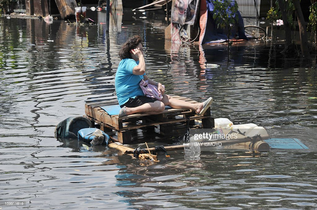A woman talks on her mobile as she travel on a flooded road using an improvised raft in Jakarta on January 23, 2013 as some areas of the capital remains submerge by flood water. A spokesman for Indonesian National Disaster Mitigation Agency (BNPB) said more than 30,000 people were still living as evacuees on January 22, while 20 people were killed during the widespread flooding that hit Jakarta that has been going on for a week. AFP PHOTO / Bay ISMOYO