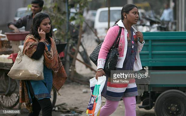 A woman talks on her mobile phone as another woman hears music on her cell phone while walking on the road Pedestrians put themselves to risk by...