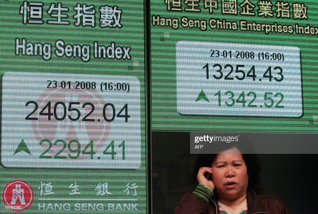 A woman talks on her mobile phone in front of a stock board displaying the Hang Seng Index in Hong Kong, 23 January 2008. Hong Kong share prices staged a spectacular recovery 23 January rallying 10.7 percent and wiping out the previous record plunge, as interest rate cuts here and in the US salvaged investor confidence, dealers said.