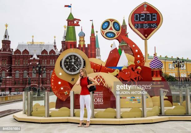 A woman talks on her mobile phone in front of the digital FIFA World Cup 2018 countdown clock placed in front of the Red Square and the Kremlin in...