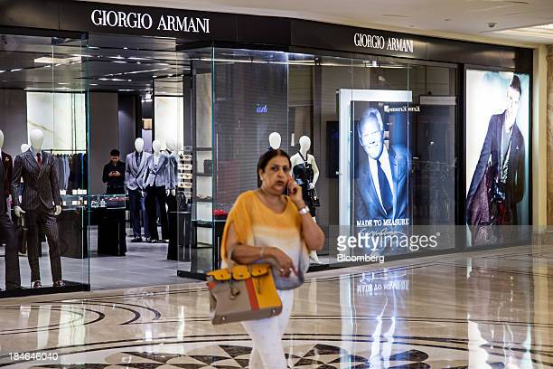 A woman talks on her mobile phone outside a Giorgio Armani SpA store at the DLF Emporio shopping mall in New Delhi India on Thursday Oct 10 2013...