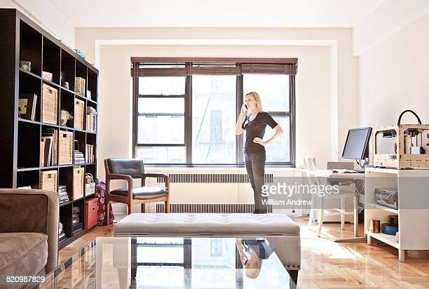 Woman talks on phone in home design studio