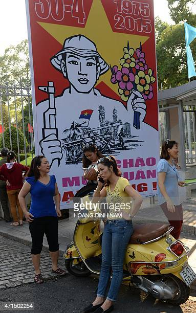 A woman talks on smartphone next to a poster marking the 40th anniversary of the fall of Saigon placed at the front gates of the former presidential...
