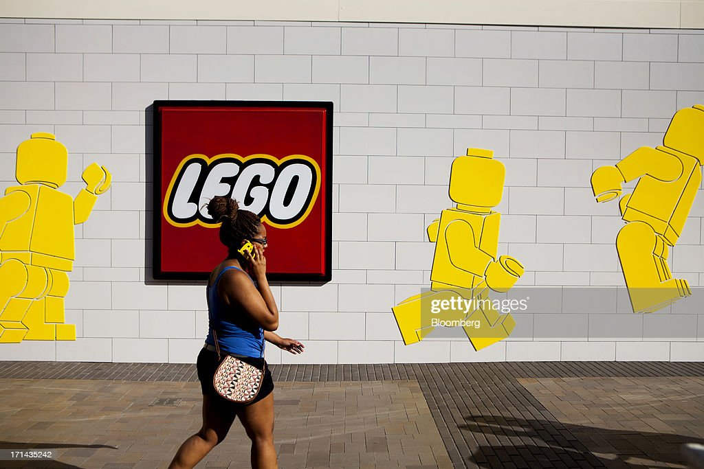 A woman talks on the phone while walking past the Lego A/S toy store aat the Fashion Valley Mall in San Diego, California, U.S., on Saturday, June 22, 2013. The Bureau of Economic Analysis is schedule to release personal consumption figures on June 26. Photographer: Sam Hodgson/Bloomberg via Getty Images