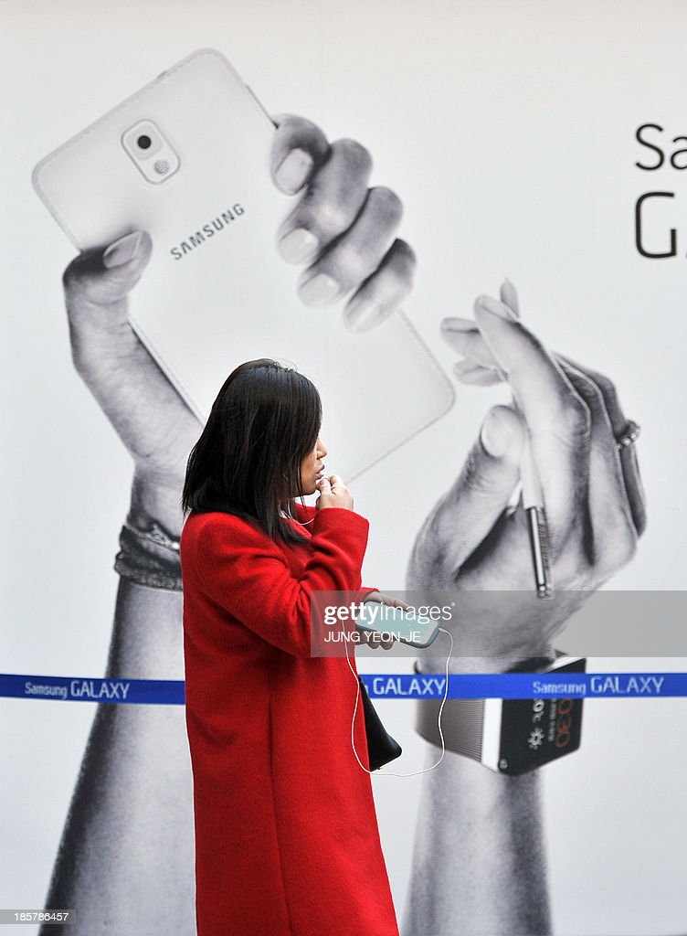 A woman talks over her phone in front of a sign board advertising Samsung Electronics' Galaxy Note 3 smartphone at a railway station in Seoul on October 25, 2013. South Korea's Samsung Electronics said its net profit spiked 25.6 percent to another record in the third quarter, driven by soaring revenue from memory chip sales.