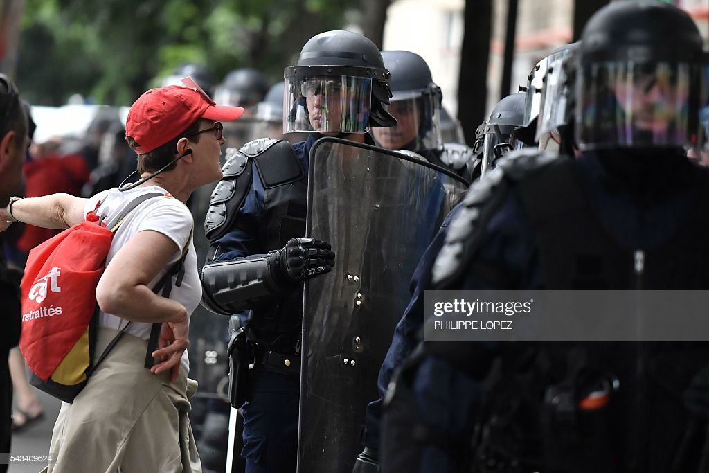 A woman talks to a French anti-riot policeman during a demonstration against controversial labour reforms, on June 28, 2016 in Paris. Thousands of people took to the streets of Paris today in the latest protest march in a marathon campaign against the French Socialist government's job market reforms. / AFP / PHILIPPE
